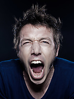 studio portrait on black background of a funny expressive caucasian man screaming