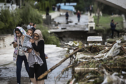 October 6, 2018 - Tonekabon, Iran - People walk past by debris after a flood caused by heavy rain in Tonekabon city, in Mazandaran province, northern Iran. Heavy rains in the northern and northwestern parts of Iran over the past two days claimed lives. (Credit Image: © Ahmad Halabisaz/Xinhua via ZUMA Wire)