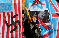 February 5, 2018 - Gaza City, Gaza Strip, Palestinian Territory - A Palestinian demonstrator burns posters depicting U.S. President Donald Trump, an Israeli, British and U.S. flags during a protest to show solidarity with Palestinian prisoners held in Israeli jails, in front of Red cross office in Gaza city.  (Credit Image: © Ashraf Amra/APA Images via ZUMA Wire)