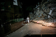 A man is seen walking during the night in the debris of Rio few kilometers from Amatrice a village where just few houses are still standing.