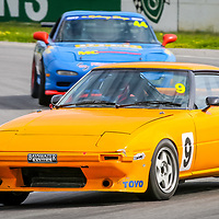 Peter Screen leading Kim Ledger through Turn 1 at Wanneroo Raceway.  Both are driving Mazda RX7 Street Cars in the combined Street Car and Improved Production race at the WA State Championship meeting hosted by the WA Sporting Car Club.