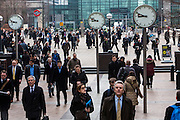 City workers walk under the clocks of Nash Court across Reuters Plaza to commute to work in Canary Wharf financial district London, England, United Kingdom.