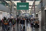 People walk through Terminal D of the Miami International Airport, Saturday, Feb. 13, 2021, in Miami.