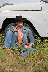 cowboy sitting against a pickup truck in a field