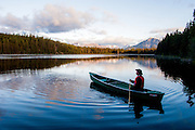 Cowboy rowing canoe in lake, Cariboo Chilcotin Coast, British Columbia, Canada