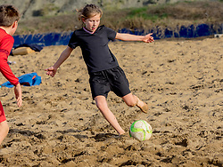 Girl and boy playing soccer on the beach