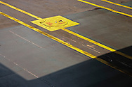 Walkways on a Washington State Ferry car deck show wear, oil spots, and rust in a graphic abstract including a hatch in the deck.