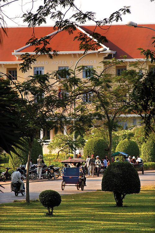 A tuktuk rolls down the road passing by the Raffles Grand Hotel d'Angkor.