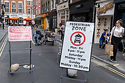 A child is picked up by its mother after falling from a twin buggy in Soho, days before the August Bank Holiday when the streets of this lively district of the capital are expected to be busy during the Coronavirus pandemic, on 26th August 2020, in London, England.