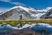A tarn reflects glacier-clad Mt Edward, Dart Glacier, and a hiker on a 20 kilometer round trip hike to Cascade Saddle from Dart Hut, in Mount Aspiring National Park, Otago region, South Island of New Zealand.