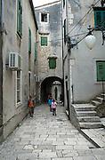 Children walking through paved backstreets of Sibenik, Croatia