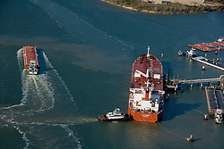 Aerial view of a tanker being guided by tugboats in Port of Houston