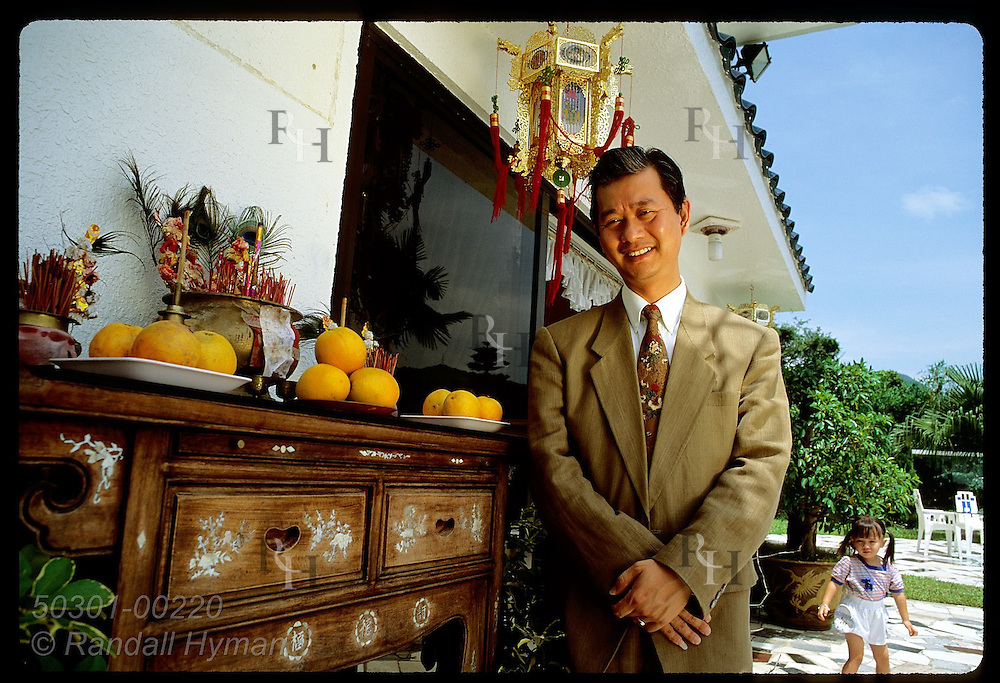 Wealthy interior designer Ma Hing Fung poses beside home altar set with daily offerings; N.T. Hong Kong