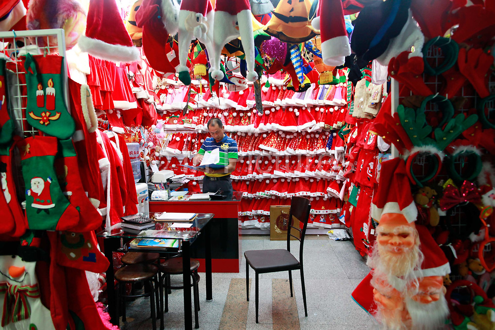 A man sits in his stall selling Santa Claus costumes and hats at the Yiwu International Trade City in Yiwu, Zhejiang Province, China on Sunday, 11 September 2011.   As the trading hub for small and medium manufacturers and exporters in the Yangtze River Delta region, Yiwu faces an uncertain future as export orders decline due to the slow economic recoveries of China's two largest trading partners, Europe and the United States