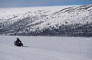 Snowmobile driving across snowy landscape