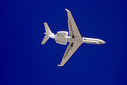 White jet plane on dark blue sky background coming in to land