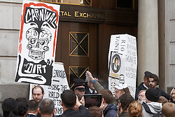 © Licensed to London News Pictures.  15/06/2012. LONDON, UK. Activists, led by a new Orleans style jazz band playing funeral songs, carry cardboard coffins protesting against human rights abuses in the mining industry. The group visited buildings associated with mining including the London Stock Exchange and the London Metal Exchange and protested against mining companies Rio Tinto, Glencore and Xstrata. In this picture: a protester pours dirt onto the steps of the London Metal Exchange. Photo credit :  Cliff Hide/LNP