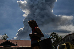 May 25, 2017 - Karo, North Sumatra, Indonesia - A resident passing as Sinabung volcano spews rolling thick volcanic ash into the air, as seen from Tiga Pancur village on May 25, 2017, North Sumatra province, Indonesia. The activity of Mount Sinabung with the status of Awas (Level IV) increases which volcanic earthquakes have continued to occur with erruptions creating an ash cloud of about 4,000 meters height. Mount Sinabung is one of the most active volcano in Indonesia. (Credit Image: © Ivan Damanik via ZUMA Wire)