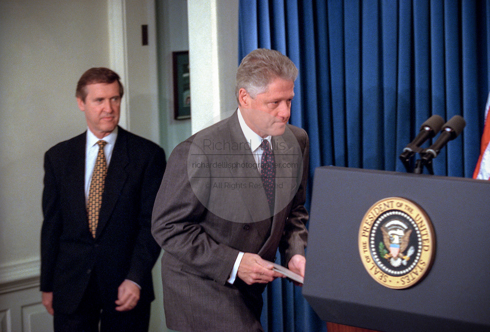 US President Bill Clinton walks to the podium in the Briefing Room of the White House November 15, 1998 in Washington, DC. Clinton announced that he called off airstrikes on Iraq after Saddam Hussein agreed to allow the UN to resume weapon inspections. Behind Clinton is Secretary of Defense William Cohen.
