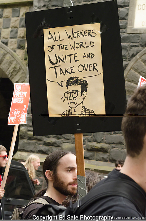 Demonstrator in 2015 May Day rally and march in Portland, Oregon holds a sign advocating workers of the world to unite an take over