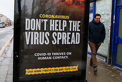 © Licensed to London News Pictures. 08/02/2021. London, UK. A man walks past government's 'Don't Help The Virus Spread' awareness publicity campaign poster on the side of a bus in north London. A major study finds that the Oxford/AstraZeneca vaccine is less effective against the South African coronavirus variant and members of the public in the UK could be required to have a third booster vaccine this year. Photo credit: Dinendra Haria/LNP