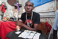 Voodoo priest Francois Michel practices voodoo in the National Cemetery in Port-au-Prince. The National Cemetery in Haiti is the base for voodoo priests. <br /> Haitian Voodoo is a syncretic religion that originates in  Haiti based upon a merging of the beliefs and practices of West African peoples with Arawakian religious beliefs, and Roman Catholic Christianity..