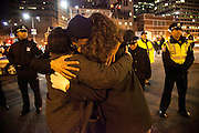 Occupy Boston members give a firm hug to each other as the Boston Police tear down the tents and arrest protesters early morning in Boston, Massachusetts, December 10, 2011.
