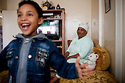 Mahmoud's grandmother looks on tenderly as Mahmoud is playing around excited at home in Sale.