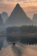 Boat heading down river at sunset and tall mountains peaks, Yangshuo, Guangxi Province, China