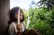 A little girl from Ban Doong ethnic village holds feathers and smiles to the camera. Phong Nha Ke Bang national park, Quang Binh Province, Vietnam, Southeast Asia