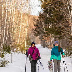 Two women preparing to go snowshoeing at Loon Echo Land Trust's Bald Pate Mountain Preserve in South Bridgton, Maine.