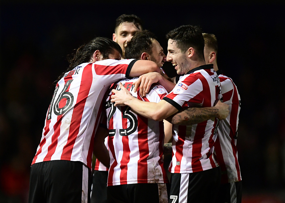 Lincoln City's Neal Eardley, centre, celebrates scoring the opening goal with team-mates Michael Bostwick, left, and Tom Pett<br /> <br /> Photographer Chris Vaughan/CameraSport<br /> <br /> The EFL Sky Bet League Two - Lincoln City v Cheltenham Town - Tuesday 13th February 2018 - Sincil Bank - Lincoln<br /> <br /> World Copyright © 2018 CameraSport. All rights reserved. 43 Linden Ave. Countesthorpe. Leicester. England. LE8 5PG - Tel: +44 (0) 116 277 4147 - admin@camerasport.com - www.camerasport.com