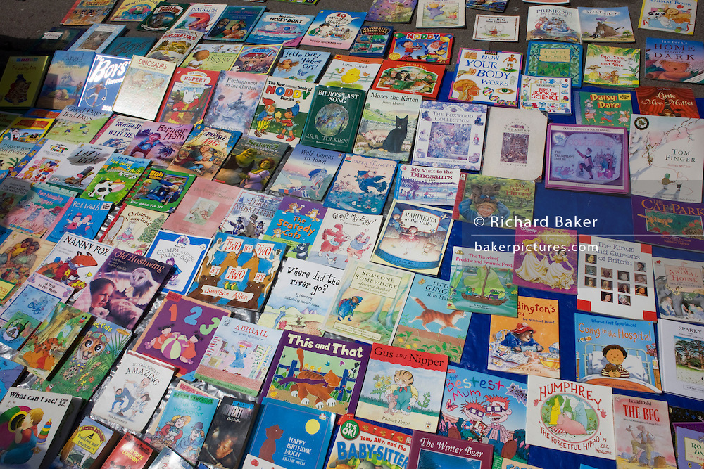 The many covers of childrens' illustrated fiction books displayed on the ground in a Brighton side-street market stall.