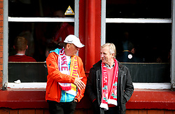 Two football fans talk outside The Albert pub before the Premier League match at Anfield, Liverpool.