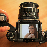 A bride is seen through the viewfinder of a classic, antique Pentax 6x7 medium-format film camera during a bridal portrait session in Columbia. <br /> <br /> Photo by Columbia SC wedding photographers Travis Bell. ©Travis Bell Photography