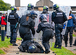 South Queensferry,, Scotland, UK. 16th September 2021. Police Scotland invite the press to witness their ongoing public order training at Craigiehall Camp at South Queensferry. The training is designed to prepare police for the upcoming COP26 event in Glasgow in November where protests are anticipated. Police in riot gear faced up  against police taking the role of protesters throwing missiles and attacking them with clubs. Pic; Injured police officer protected by colleagues.  Iain Masterton/Alamy Live News.