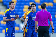 PENALTY AFC Wimbledon defender Ben Heneghan (22) and AFC Wimbledon defender Will Nightingale (5) plead with referee Craig Hicks during the EFL Sky Bet League 1 match between AFC Wimbledon and Hull City at Plough Lane, London, United Kingdom on 27 February 2021.