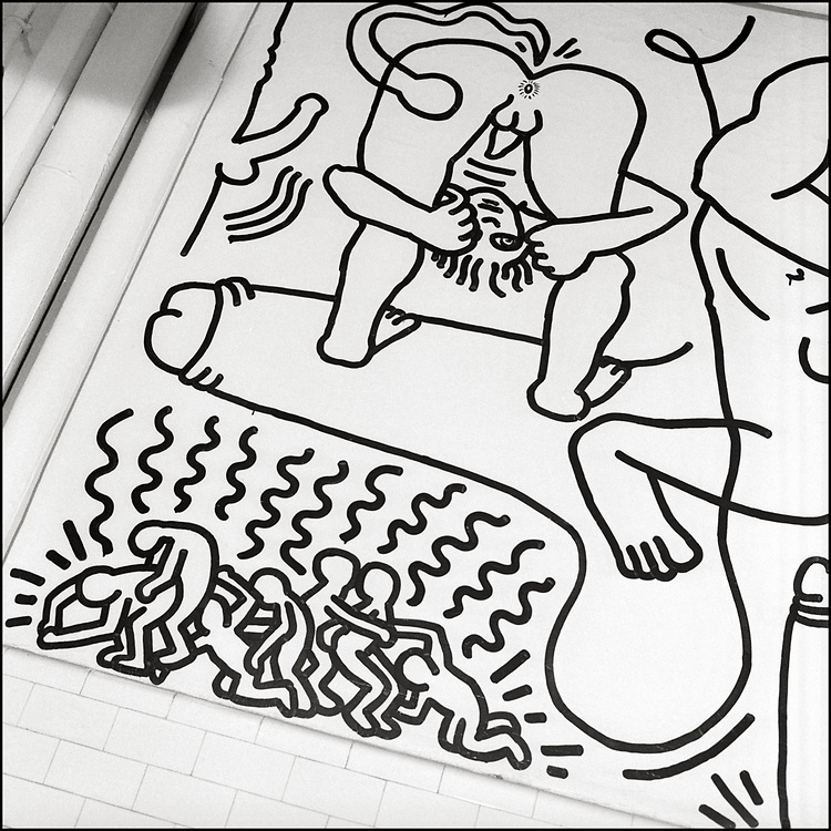 """In May 1989 Keith Haring created the bathroom mural """"Once Upon a Time"""". He was 31 at the time and this was his last major mural before his death in February 1990 of AIDS. The piece was created for """"The Center Show,"""" a celebration of the 20th anniversary of the Stonewall Riots. The Center Show called upon LGBT artists to create site-specific works of art in the building commonly called """"The Center"""" (now called The Center: Lesbian, Gay, Bisexual & Transgender Community Center). Haring chose to create his provocative work in the second floor men's bathroom.<br /> <br /> The mural covers four interior walls with Haring's signature black-on-white line drawings of penises, fluids, babies, and groping figures all intertwined above the tiles of the bathroom stalls."""