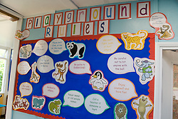 Playground rules' display on wall in school classroom,
