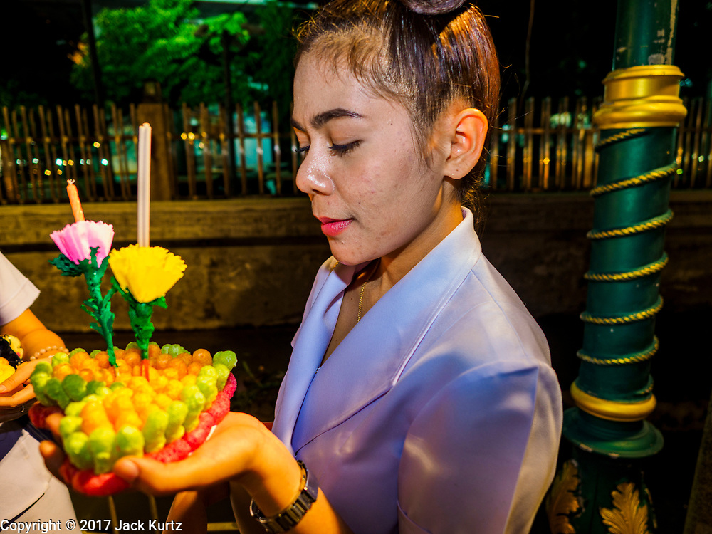 """03 NOVEMBER 2017 - BANGKOK, THAILAND:  A woman prays before floating her krathong during Loi Krathong at Wat Prayurawongsawat on the Thonburi side of the Chao Phraya River. Loi Krathong is translated as """"to float (Loi) a basket (Krathong)"""", and comes from the tradition of making krathong or buoyant, decorated baskets, which are then floated on a river to make merit. On the night of the full moon of the 12th lunar month (usually November), Thais launch their krathong on a river, canal or a pond, making a wish as they do so. Loi Krathong is also celebrated in other Theravada Buddhist countries like Myanmar, where it is called the Tazaungdaing Festival, and Cambodia, where it is called Bon Om Tuk.    PHOTO BY JACK KURTZ"""