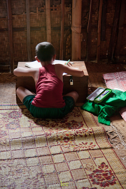 A young boy studies English at his home, a house on stilts built in the middle of the massive Inle Lake in Shan state, Myanmar