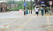 A flash flood fills the streets after a line of thunderstorms moved through Wayne. Pa., Monday, June 10, 2013