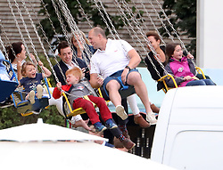 Mike Tindall takes daughter Mia on a fairground ride at the Gloucestershire festival of polo at Beaufort Polo Club in Gloucestershire.<br /><br />11 June 2017.<br /><br />Please byline: Vantagenews.com<br /><br />UK clients should be aware children's faces may need pixelating.