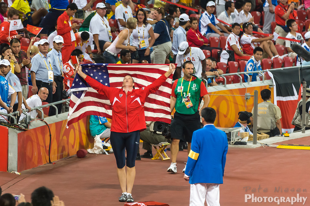 Olympic athlete Stephanie Trafton Brown takes a victory lap and stops to display the American flag