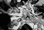 """""""The week of Dunblane.""""  Mindful of the Dunblane massacre that week, a baby massage class takes place at a health clinic in south London. Spread across a matt are six babies of varying ages and sizes whose mums are tenderly stroking their infants' bodies and senses with soft, gentle touches over the head, face, shoulders, arms, chest, stomach and legs which is a recommended way of tactile communication between mother and child. Some children are looking up into their mothers' faces, others are looking elsewhere and one is upset but comforted. This is from a documentary series of pictures about the first year of the photographer's first child Ella. Accompanied by personal reflections and references from various nursery rhymes, this work describes his wife Lynda's journey from expectant to actual motherhood and for Ella - from new-born to one year-old..."""
