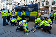 Police officers carry a search operation on climate activists from Extinction Rebellion during the group's 'Impossible Rebellion' series of actions at Oxford Circus in central London, on Wednesday, August 25, 2021. - Climate change demonstrators from environmental activist group Extinction Rebellion continued with their latest round of protests in central London, promising two weeks of disruption. (VX Photo/ Vudi Xhymshiti)