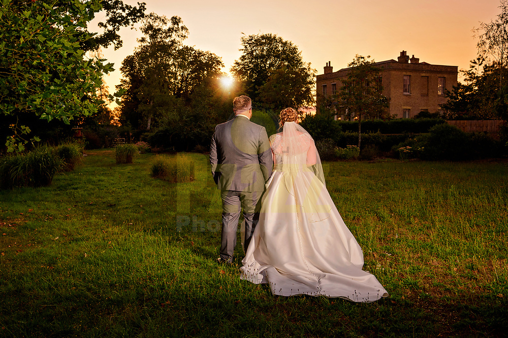 Beautiful photograph of the bride and groom taking a romantic walk in the grounds at Shortmead House.