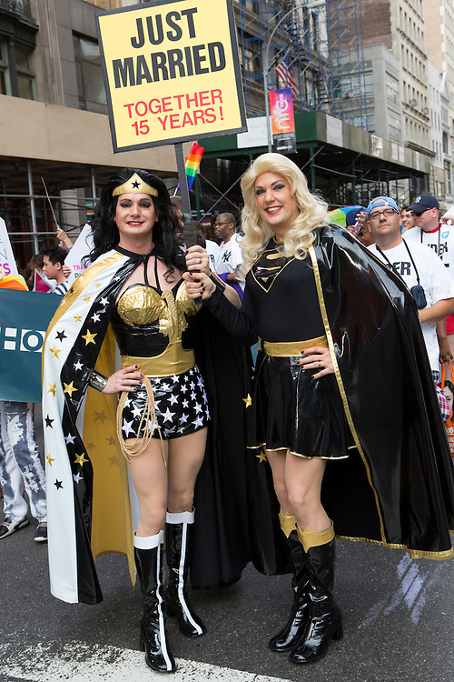 """A transgendered couple wear elaborate costumes somewhat similar to those of Wonder Womanand Superwoman. They carry a sign that reads """"Just Married Together 15 years!"""""""