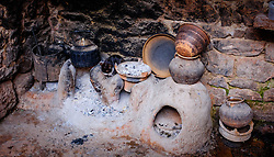 A cat sits by the fire and cooking pots in a Berber house in the Ourika Valley in Morocco, North Africa<br /> <br /> (c) Andrew Wilson | Edinburgh Elite media