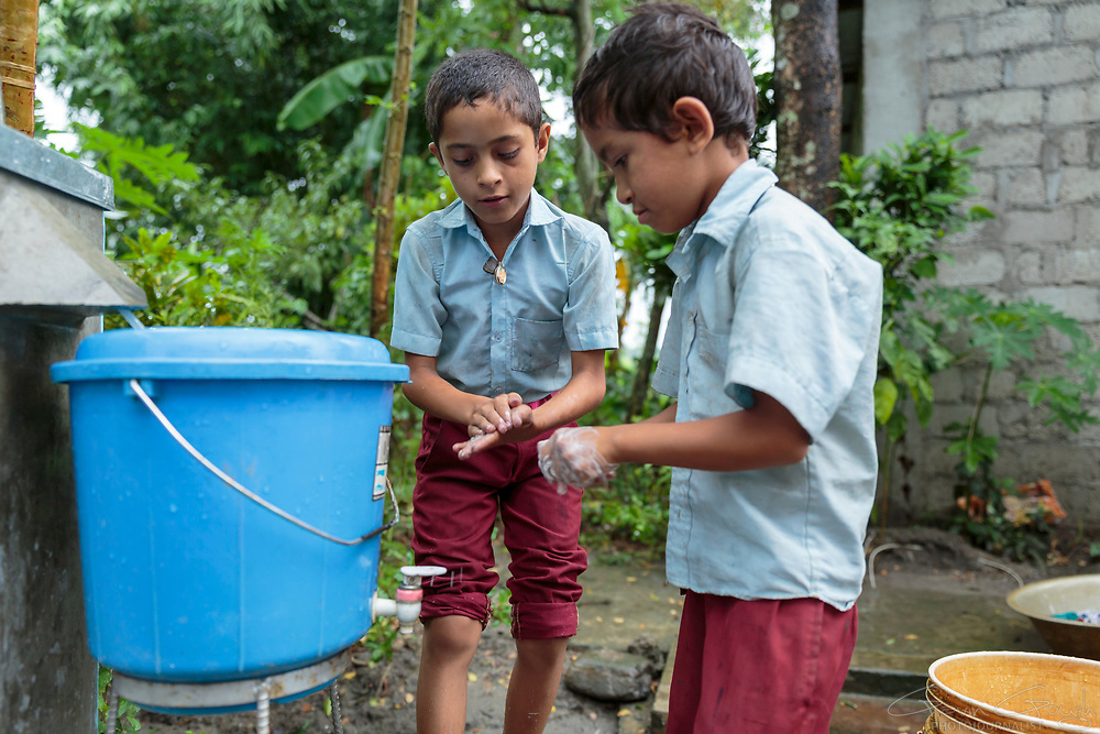 Before dinner, Chandramani Karki and Rajes Thapa wash their hands in the water from a biosand water filter. Educating families about the importance of hygiene and sanitation ensures that they can make the most of their clean water supply.